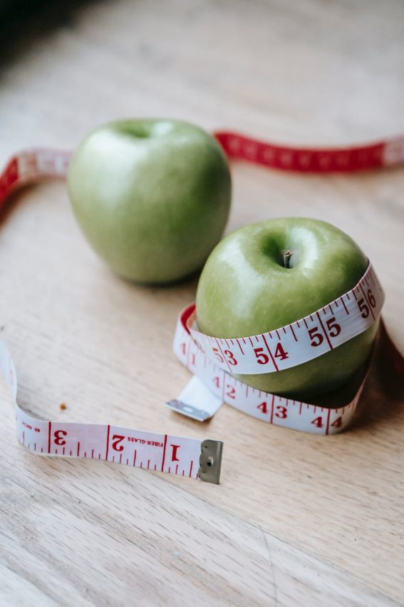 apples with measuring tape on table